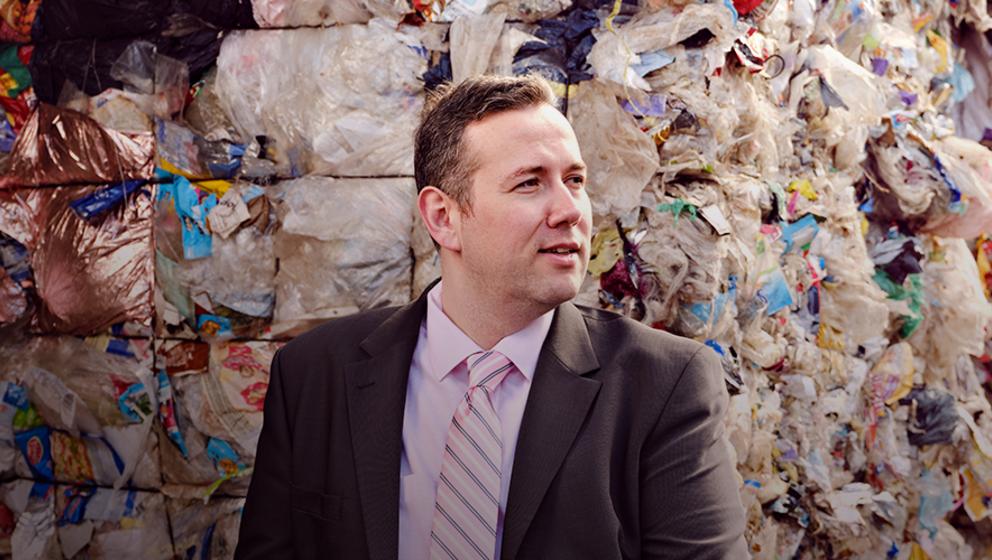man framför sopor av plast